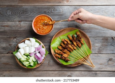 Overhead view people holding chicken satay dipping peanut sauce on wooden dining table, one of famous local dishes.