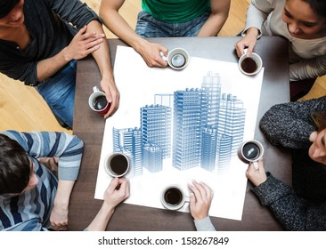 Overhead view of people sitting around table while having cup of coffee