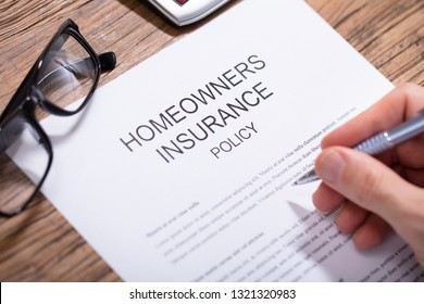 Overhead View Of A Person's Hand Filling Homeowners Insurance Policy Form Over Wooden Desk