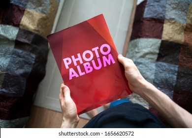 overhead view of person's hands holding the red photo album book, family nostalgia