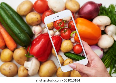 Overhead view of phone taking photo of a set of vegetables. Greens; vegetables and fruits on white background view from above with copy space