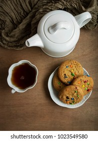 A overhead view of a plate of cookies with chocolate candy bits and a cup of tea and teapot.