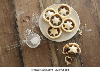 Overhead view of a plate of decorative freshly baked Christmas mince pies with pastry stars alongside a half eaten pie and strainer with icing sugar to dust the top