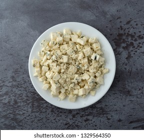 Overhead view of a portion of crumbled blue cheese on a white plate atop a gray background illuminated with natural lighting.