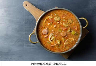 Overhead view of a pot of gumbo on a cutting board.