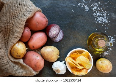 Overhead view of potatoes with crisps red onion, olive oil, garlic and rock salt, on slate table with copy space