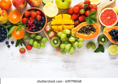 Overhead view of rainbow colored fruits, strawberries, blueberries, mango, orange, grapefruit, banana, apple, grapes, kiwis on the white background, copy space for text, selective focus