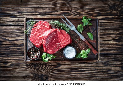 overhead view of raw beef steaks with peppercorns, fresh basil leaves, rosemary, salt and bbq fork on a rude cutting board on an old rustic wooden table, horizontal view from above