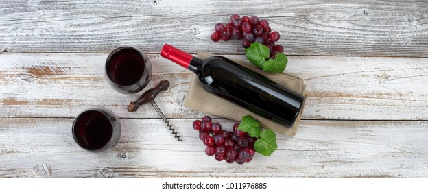 Overhead view of Red wine bottle with grapes, filled drinking glasses and corkscrew on weathered wooden boards
