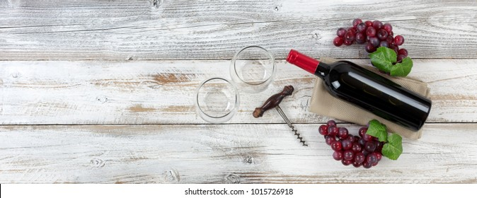 Overhead view of Red wine bottle with grapes, empty drinking glasses and corkscrew on weathered wooden boards