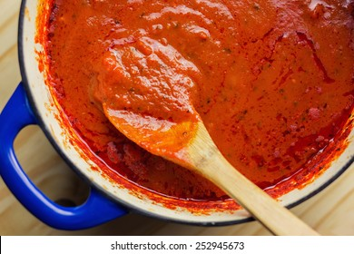 Overhead view of  rich marinara sauce slow cooked all day in an enamel coated cast iron Dutch oven.