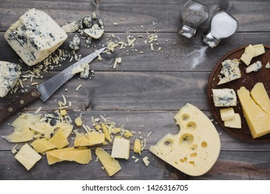 An overhead view of salt and pepper shaker with cheese on wooden desk