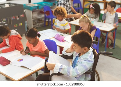 Overhead view of school kids studying in the classroom at school against teacher helping a mixed-race schoolgirl in background