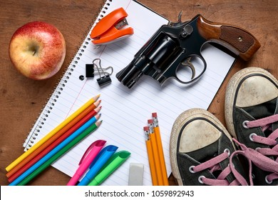 overhead view of school supplies and a gun on a desk