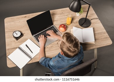 overhead view of schoolboy doing homework on laptop at table with textbook, book, plant, lamp, clock, apple and glass of juice