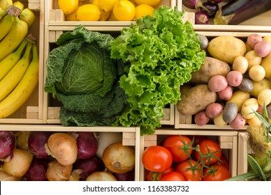 Overhead view of separated rectangular wooden boxes of random produce including lettuce and bananas next to each other