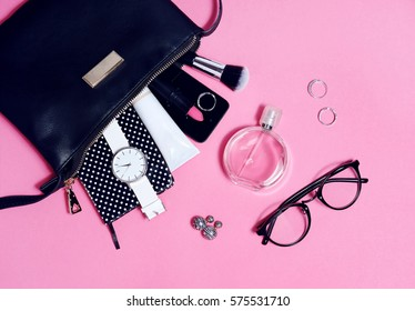 Overhead view of set female essential beauty items on pink flat lay