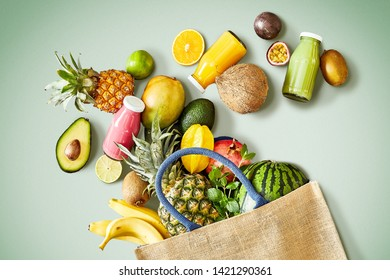 Overhead view of several different kinds of healthy fruit falling out of environmentally friendly canvas bag