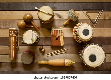 Overhead view of several hand drums and other percussion instruments from various cultures.  The picture is a balanced layout on natural wood planks in a soft light.