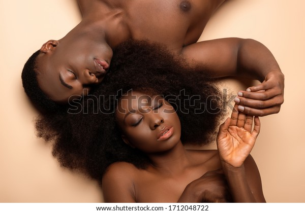 overhead view of sexy naked african american couple lying with closed eyes on beige