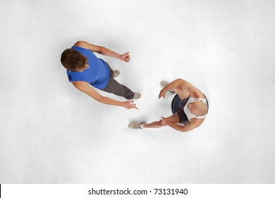 Overhead View Of Sitting Man Listening To His Personal Trainer In Gym