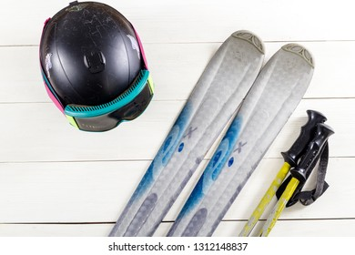 Overhead view of ski accessories placed on rustic white wooden table. Items included ski, goggles, helmet and ski sticks. Winter sport leisure time concept.