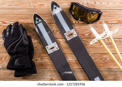 Overhead view of ski accessories placed on rustic old wooden table. Items included ski, goggles, gloves and ski sticks. Winter sport leisure time concept.