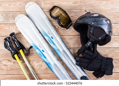 Overhead view of ski accessories placed on rustic wooden table. Items included helmet, goggles, gloves, ski and sticks. Winter sport leisure time concept.