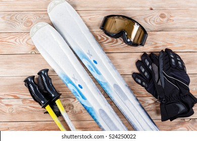 Overhead view of ski accessories placed on rustic wooden table. Items included ski, goggles, gloves and ski sticks. Winter sport leisure time concept.