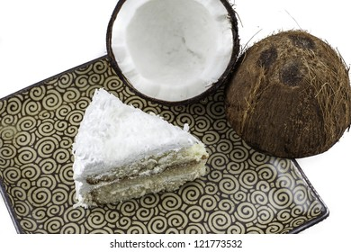 Overhead view of a slice of coconut cake on a plate with a crack coconut next to it.