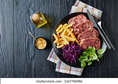 overhead view of sliced beef tongue and meat aspic served with french fries, green leaves and red cabbage salad on a black plate on a wooden table with mustard in a bowl, view from above, flatlay