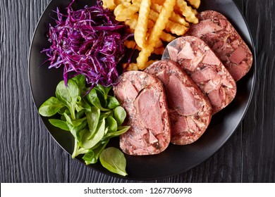overhead view of sliced beef tongue and meat aspic served with french fries, green leaves and red cabbage salad on a black plate on a wooden table, view from above, flatlay, close-up