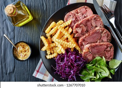 overhead view of  sliced beef tongue aspic served with french fries, green leaves and red cabbage salad on a black plate on a wooden table with mustard in a bowl, view from above, flatlay, close-up