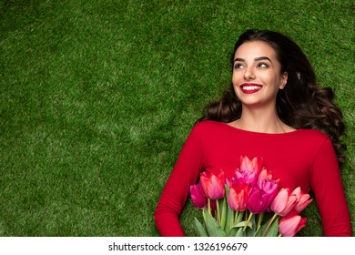 Overhead view of smiling brunette in red dress lying in grass with tulips in hands and looking away