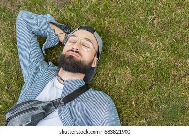overhead view of smiling man with eyes closed lying on grass