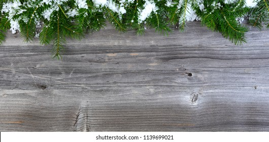 Overhead view of snow covered Christmas fir tree branches on weathered wood for holiday concept