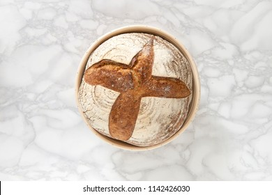 Overhead view of a sourdough bread in bowl on marble background