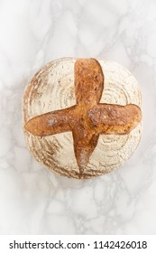 Overhead view of a sourdough bread on marble background