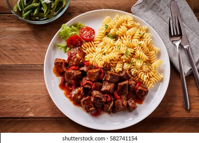 Overhead view of spicy hungarian beef in sauce served beside plain spiral pasta