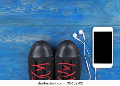 Overhead view of sports shoes by mobile phone with isolated screen and in-ear headphones on blue wooden table, floor. Empty space for text, copy space, empty blank screen