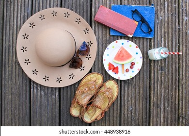 Overhead view of summer feminine objects on old wooden deck, including sun hat, sunglasses, old books, sandals and a healthy snack