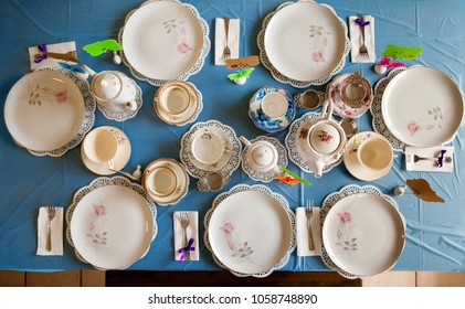 Overhead view of a table set for a tea party.  Mismatched plates, cups, and tea pots sit atop doilies and a blue, platic table cloth.  There are blank name cards for guests.