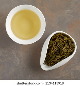 Overhead view of tea cup and bowl with dry tea on the table
