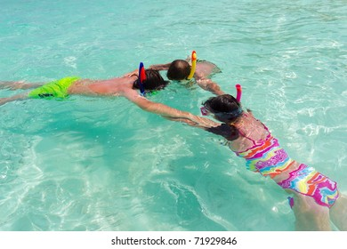 Overhead view of three children snorkeling in turquoise sea.