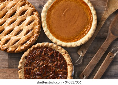 Overhead view of three pies for a Thanksgiving Holiday feast. Pecan, Apple and Pumpkin in horizontal format on wood table
