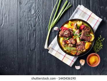 overhead view of traditional Jamaican Curry Goat – slow cooked Jamaican Spiced meat and vegetables spicy Curry in a black bowl on a rustic wooden table, view from above, flat lay, copy space, close-up