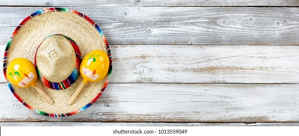 Overhead view of traditional maracas on top of a large sombrero for Cinco de Mayo holiday celebration on weathered white wooden boards
