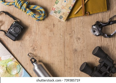 Overhead view of travel equipment for an adventure trip on wooden floor with copy space. Adventure travel concept.