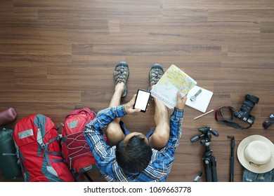 Overhead view of traveler man plan and backpack planning vacation travel idea concept trip with holding map and smart phone. Top view.