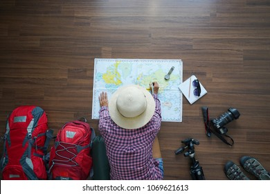 Overhead view of traveler woman plan and backpack planning vacation trip with map. Top view.